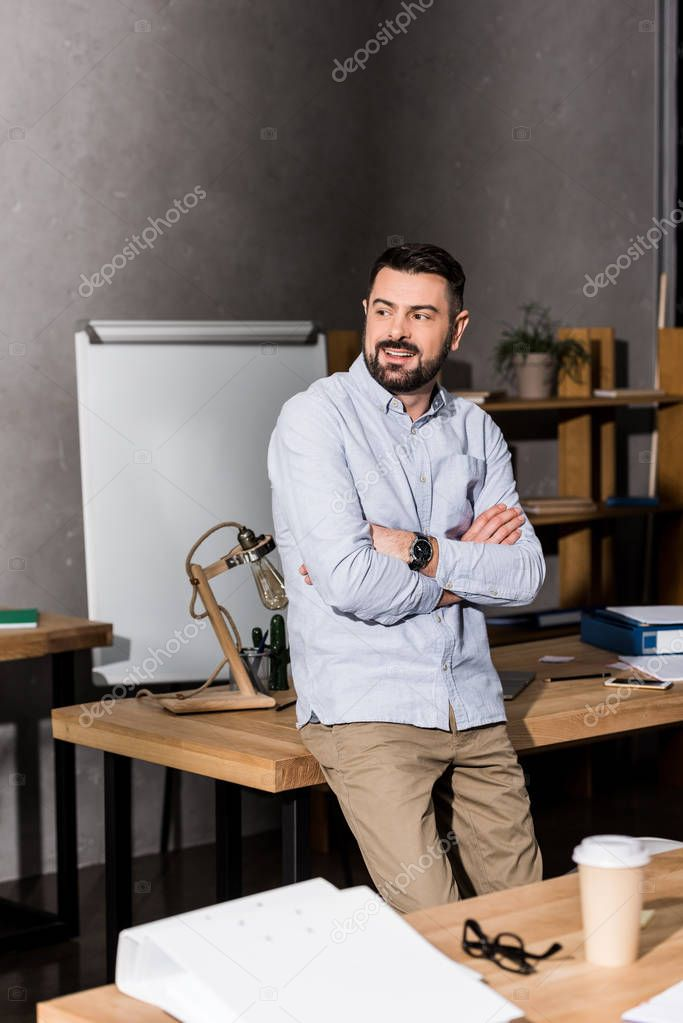 smiling businessman with crossed hands leaning on table in office and looking away