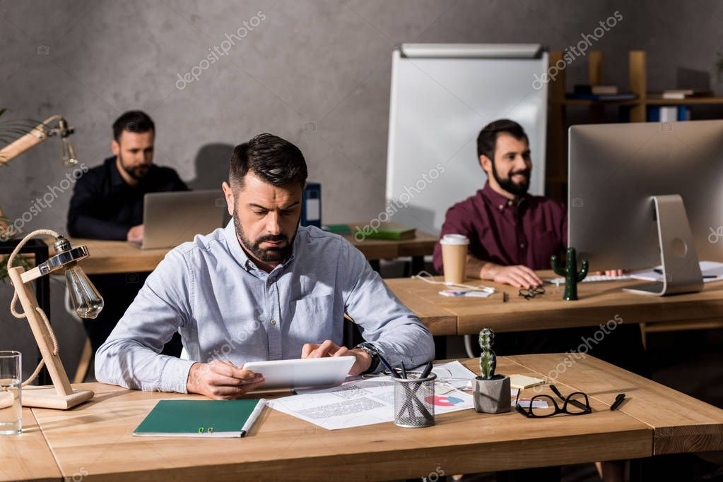 businessmen sitting at working tables with different digital devices