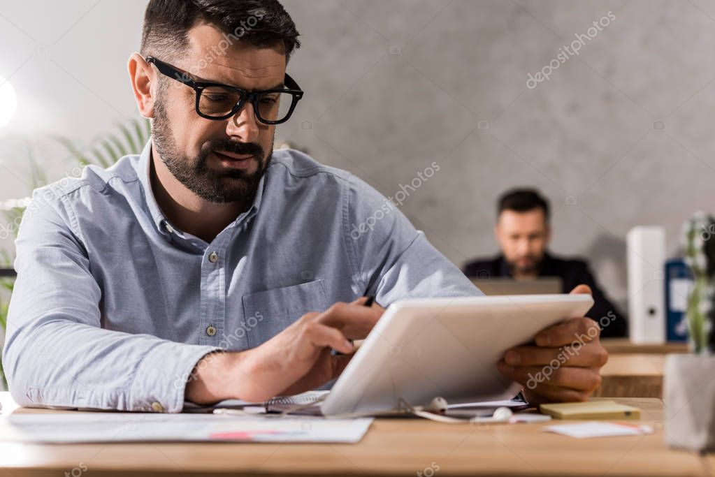 handsome businessman working with tablet in office