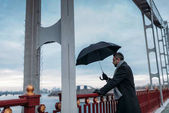 Fotografie handsome lonely man with umbrella standing on bridge