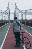 Hátulnézet, elegáns férfi kerékpár álló gyalogos híd