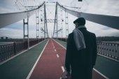 Fotografie elegantní muž v kabát a šátek s kufrem stojící na most pro pěší