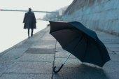 Fotografie deštník, ležící na břehu řeky, zatímco muž rozmazané na pozadí