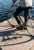 cropped shot of man standing on river shore with bicycle