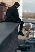 schöner Mann mittleren Alters sitzt auf Hausdach