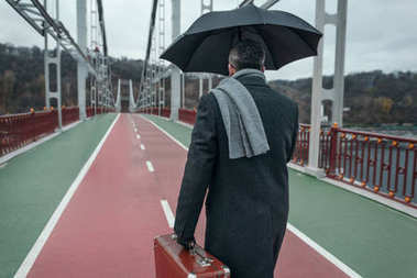 stylish man with umbrella and luggage walking by pedestrian bridge