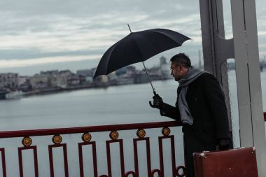 adult man with umbrella and luggage walking by bridge