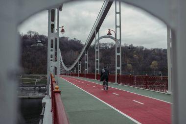 Stylish man riding bicycle on pedestrian bridge stock vector