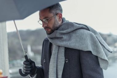 lonely sad man in scarf with umbrella walking under rain