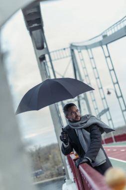 Stylish adult man in scarf with umbrella on bridge stock vector