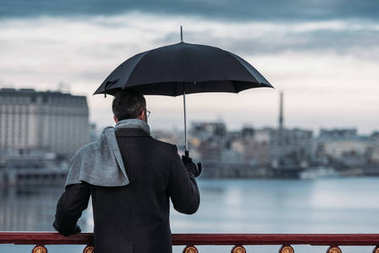 back view of lonely man with umbrella standing on bridge