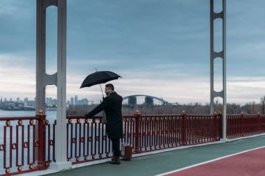 stylish lonely man with umbrella and suitcase standing on bridge