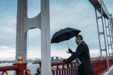 handsome lonely man with umbrella standing on bridge