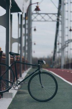 Vintage bike on pedestrian bridge on cloudy day stock vector