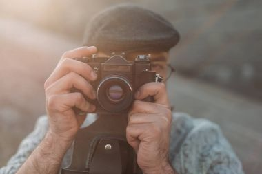 stylish man taking photo with vintage film camera
