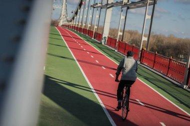 stylish man riding bicycle on pedestrian bridge with biking road