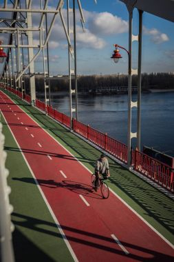 high angle view of adult man riding bicycle on pedestrian bridge over river