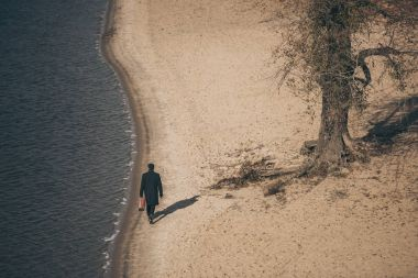 high angle view of man with suitcase walking by sandy beach in autumn
