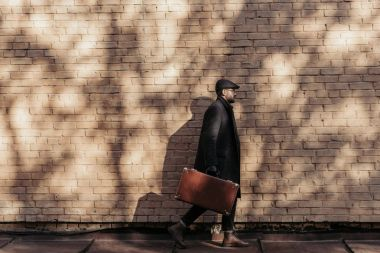 side view of adult man with suitcase walking in front of brick wall