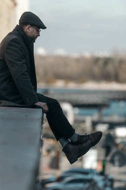lonely middle aged man sitting on roof of building