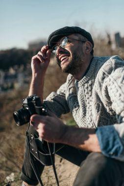happy adult man with vintage film camera sitting on rural road