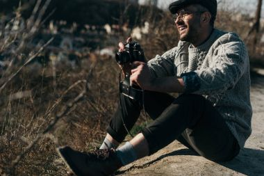 handsome adult man with vintage film camera sitting on rural road