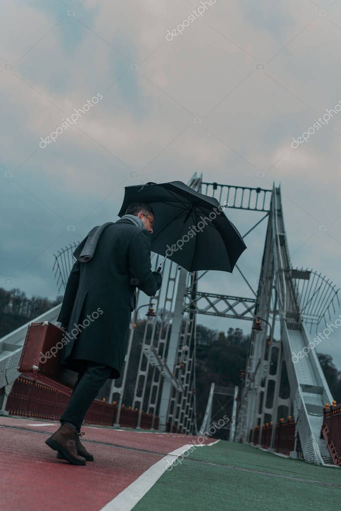 bottom view of handsome middle aged man with umbrella and luggage walking by pedestrian bridge