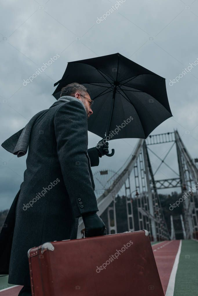 bottom view of middle aged man with umbrella and luggage walking by pedestrian bridge