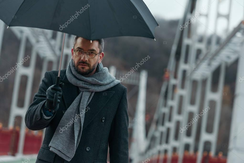 handsome middle aged man with umbrella walking by bridge