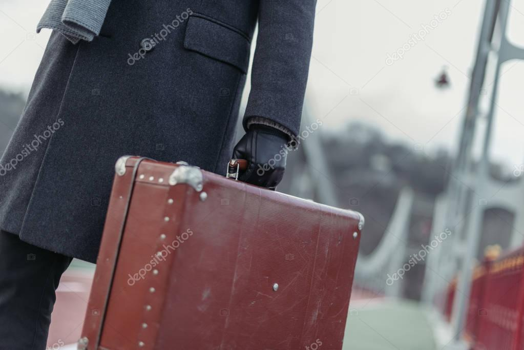 cropped shot of man in coat and gloves with suitcase