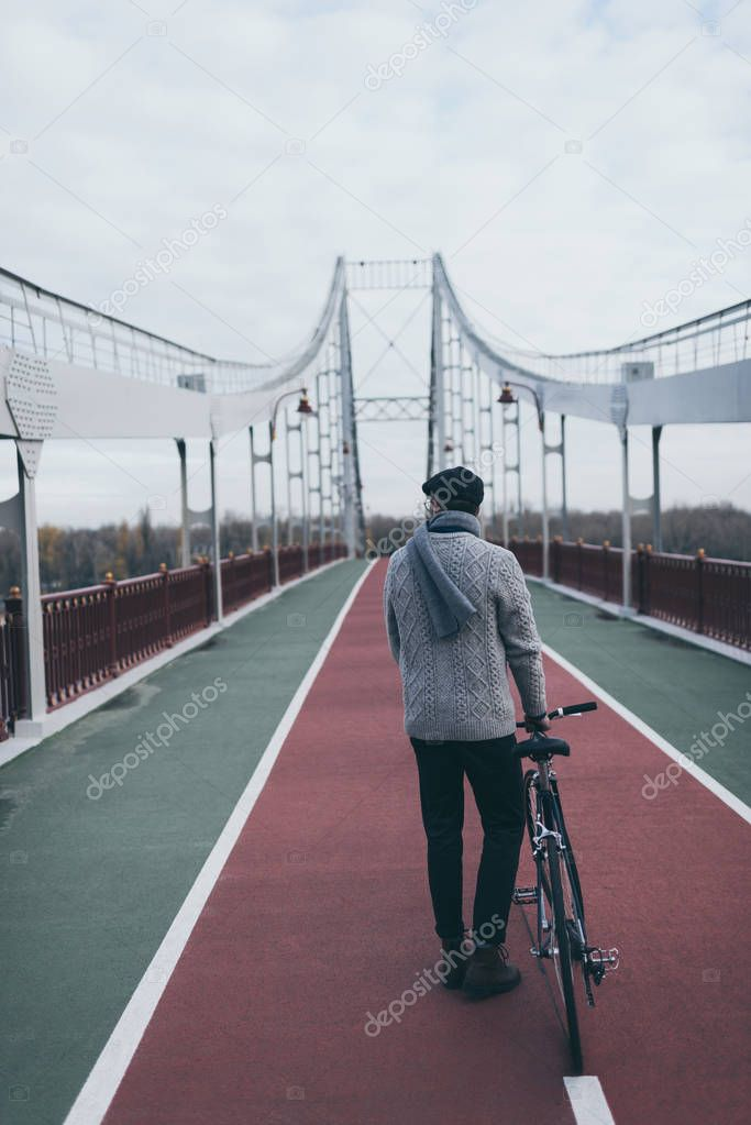 back view of stylish man with bicycle standing on pedestrian bridge