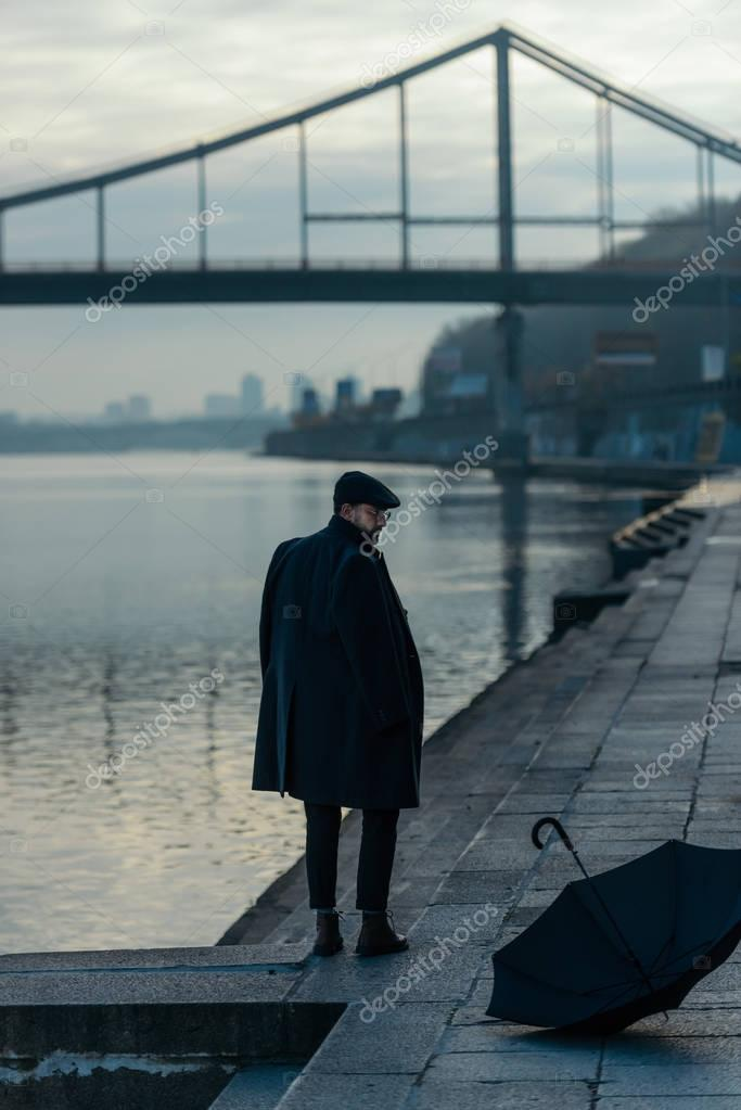 handsome middle aged man looking at umbrella lying on river shore