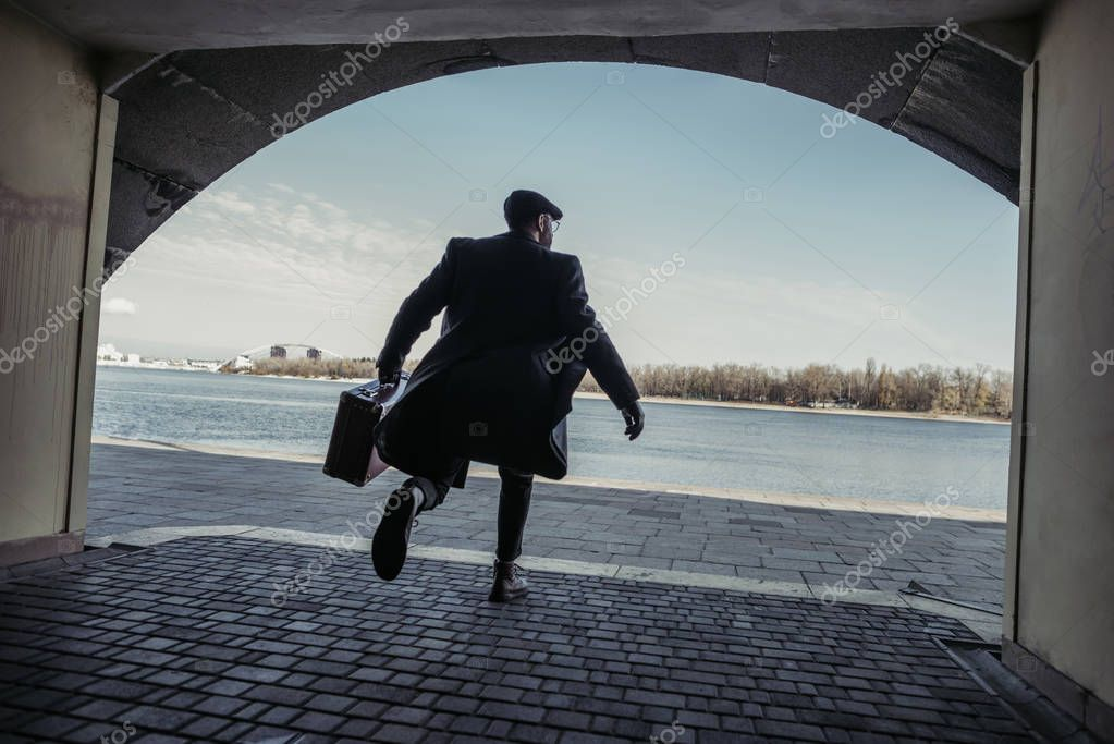 stylish man with suitcase running out tunnel to river shore