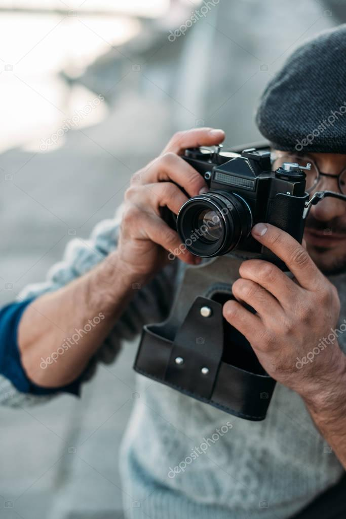 close-up shot of handsome adult man with vintage film camera outdoors