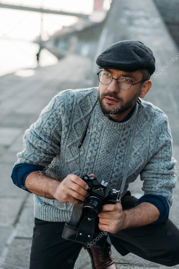handsome adult man with vintage film camera outdoors