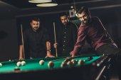 Fotografia azienda di giovani uomini bei successo giocando in piscina russa presso bar