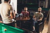 Fotografia giovane uomo caucasico seduto sul divano e bere birra accanto al tavolo da biliardo nel bar