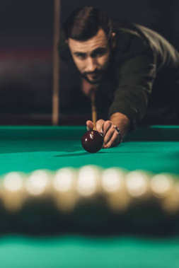 front view of handsome man playing russian pool at bar