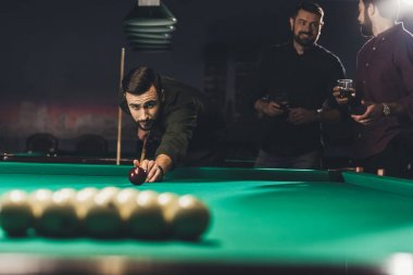 handsome man playing in pool at bar with friends