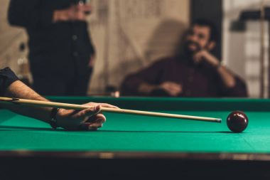 cropped image of successful man playing in pool at bar with friend