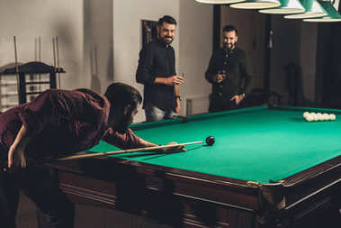 successful man playing in pool at bar with friends