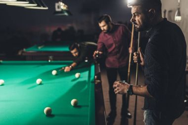 company of handsome men playing in pool at bar