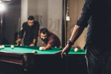 cropped image of successful handsome men playing in pool at bar