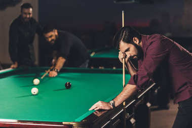 upset caucasian man with cue beside pool table at bar with friends