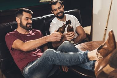 young caucasian men sitting on couch and drinking beer beside billiard table in bar