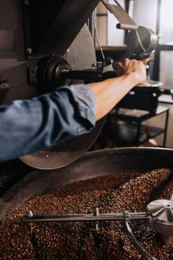partial view of coffee roaster working on roasting machine