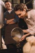 Fotografie Selektivní fokus ženy nalil kávová zrna do pečení stroj
