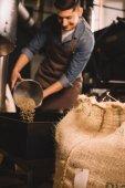 Fotografie Selektivní fokus pražírna kávy přelijete kávová zrna do pečení stroj