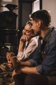 usmívající se pár s šálky kávy mají přestávku během práce v kavárně