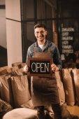 Fotografie Coffee-Shop Arbeiter mit Schild geöffnet Blick in die Kamera Lächeln